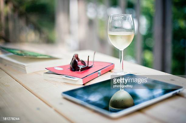 Books and glass of wine on outdoor table top