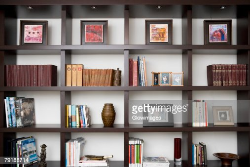 Books and picture frames in shelves : Foto de stock