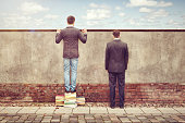 One man is expanding his horizon by standing on a stack of books. While the other is facing the wall.