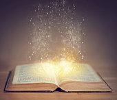 Shot of an open book with sparkles coming out of it