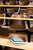 Books on desk and empty chairs in lecture hall