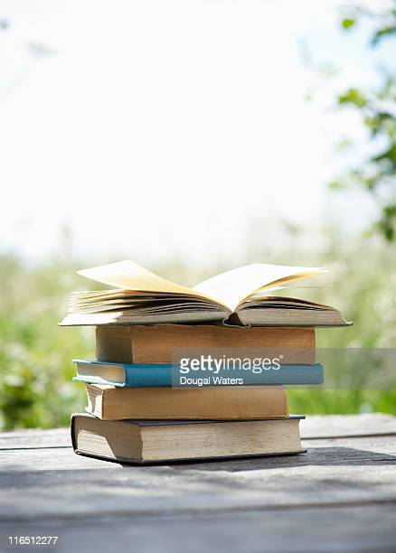 Books stacked up on garden table.
