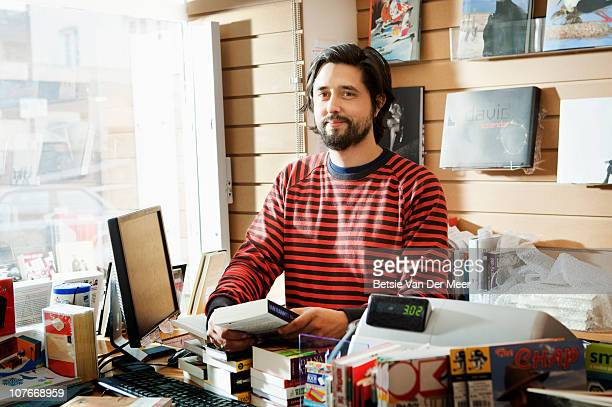 Bookseller behind counter in bookshop.