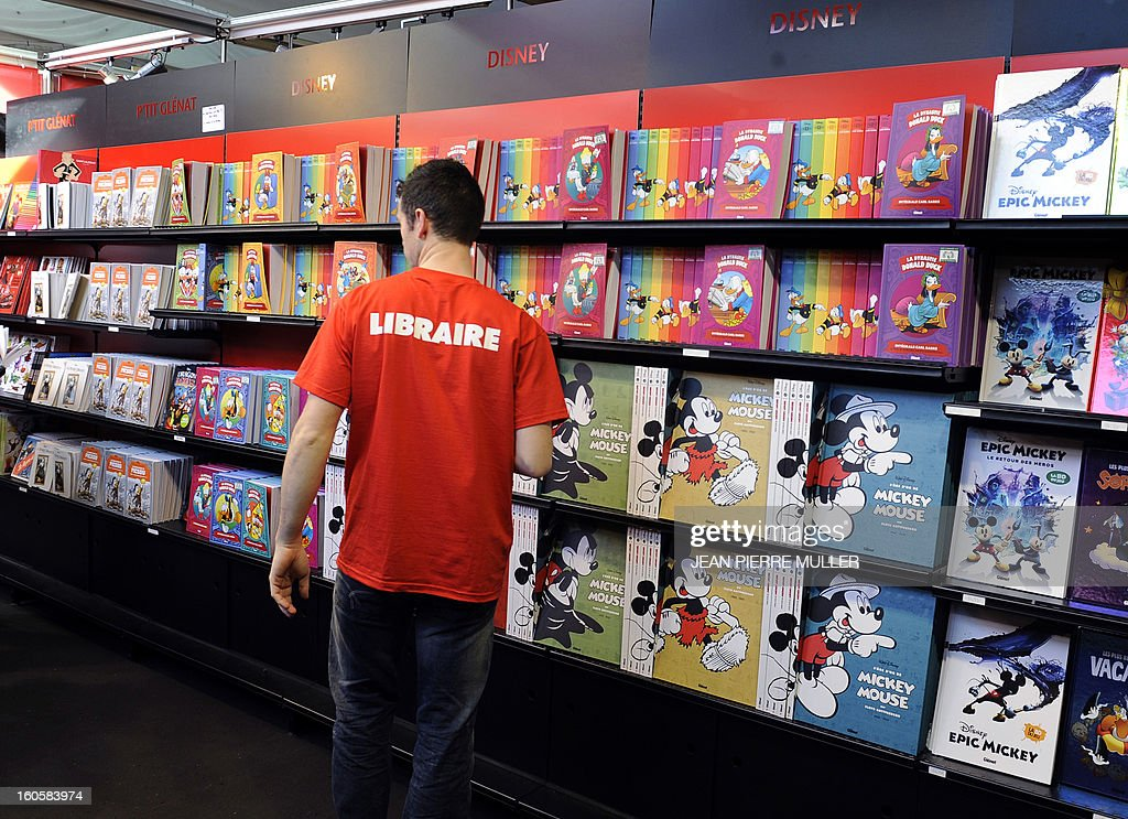 A bookseller checks his comic books on shelves on the last day during the Comic book festival of Angouleme on February 3, 2013 in Agouleme, western France. The awards ceremony will take place today. AFP PHOTO JEAN PIERRE MULLER.