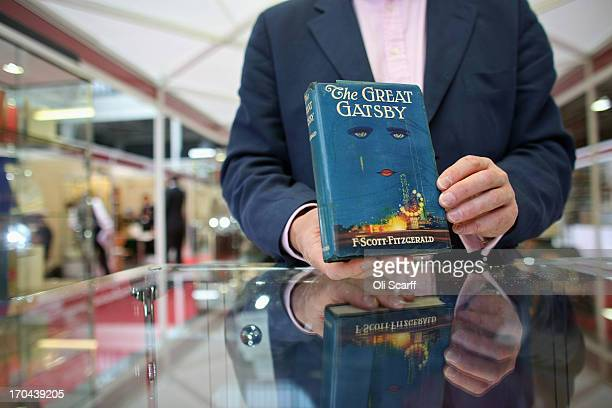 A bookseller holds a first edition of F Scott Fitzgerald's 'The Great Gatsby' at the London International Antiquarian Book Fair in the Olympia...