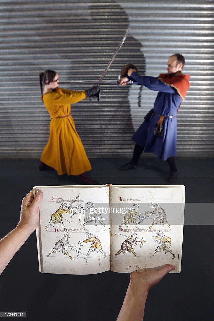 A bookseller holds a modern reproduction of 'I.33', a manuscript describing the skills of medieval swordsmanship dating from 1310, at the London International Antiquarian Book Fair in the Olympia exhibition centre on June 13, 2013 in London, England. The original manuscript is held in the Royal Armouries museum. The Antiquarian Booksellers' Association was founded in 1906 and their book fair is the oldest in the UK having run for 56 years. It attracts approximately 200 book dealers from around the world, selling fascinating and rare books, maps, prints and manuscripts.