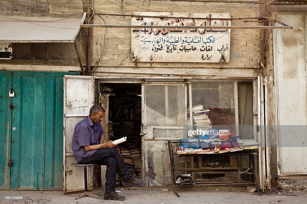 A bookseller reads at his stall in the Muntanabi Street area on March 29, 2013 in Baghdad, Iraq. Ten years after the regime of Saddam Hussein was toppled from power, Baghdad continues to show the scars of the war. In vast areas, infrastructure is fractured and basic services are lacking, however, some areas of the capital are showing promising signs of recovery.