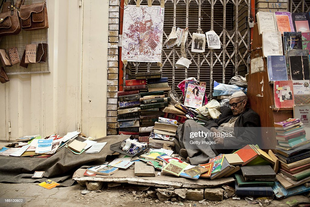A bookseller sleeps at his stall in the Muntanabi Street area on March 29, 2013 in Baghdad, Iraq. Ten years after the regime of Saddam Hussein was toppled from power, Baghdad continues to show the scars of the war. In vast areas, infrastructure is fractured and basic services are lacking, however, some areas of the capital are showing promising signs of recovery.