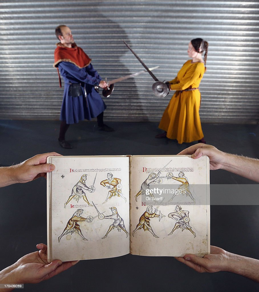 Booksellers holds a modern reproduction of 'I.33', a manuscript describing the skills of medieval swordsmanship dating from 1310, at the London International Antiquarian Book Fair in the Olympia exhibition centre on June 13, 2013 in London, England. The original manuscript is held in the Royal Armouries museum in Leeds. The Antiquarian Booksellers' Association was founded in 1906 and their book fair is the oldest in the UK having run for 56 years. It attracts approximately 200 book dealers from around the world, selling fascinating and rare books, maps, prints and manuscripts.
