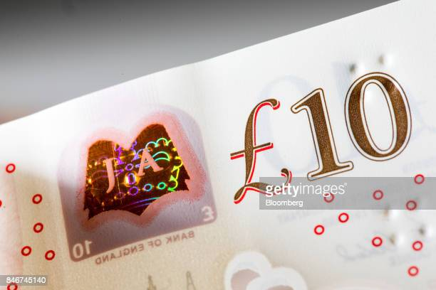 A bookshaped copper foil patch containing the letters 'JA' sits on the new UK 10pound banknote in this arranged photograph taken at the Bank of...
