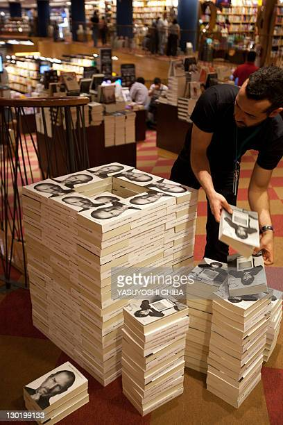 A bookshop employee piles up copies of a biography of the late 'Apple' cofounder Steve Jobs in Sao Paulo Brazil on October 24 2011 The eagerly...