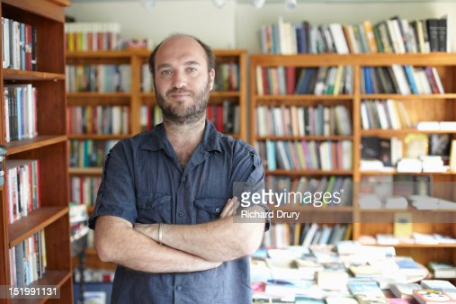 Bookshop owner in his shop : Stock Photo