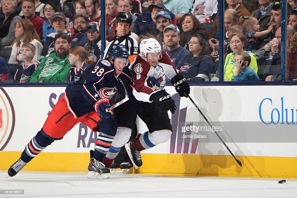Boone Jenner #38 of the Columbus Blue Jackets and Erik Johnson #6 of the Colorado Avalanche skate after a loose puck during the third period on April 1, 2014 at Nationwide Arena in Columbus, Ohio. Colorado defeated Columbus 3-2 in overtime.