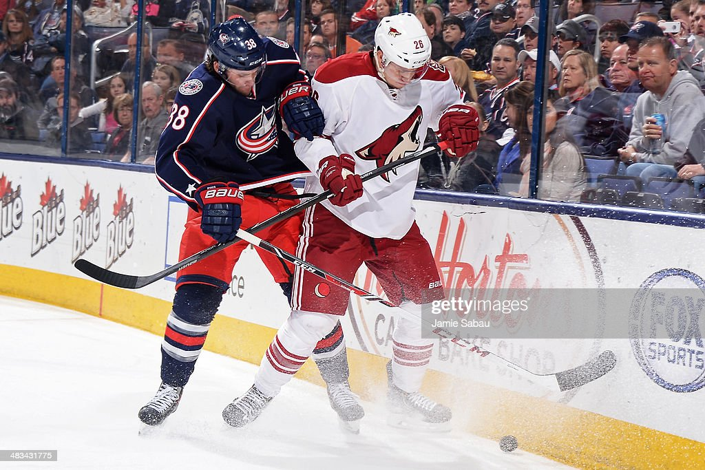 Boone Jenner #38 of the Columbus Blue Jackets and Michael Stone #26 of the Phoenix Coyotes battle for a loose puck during the first period on April 8, 2014 at Nationwide Arena in Columbus, Ohio.