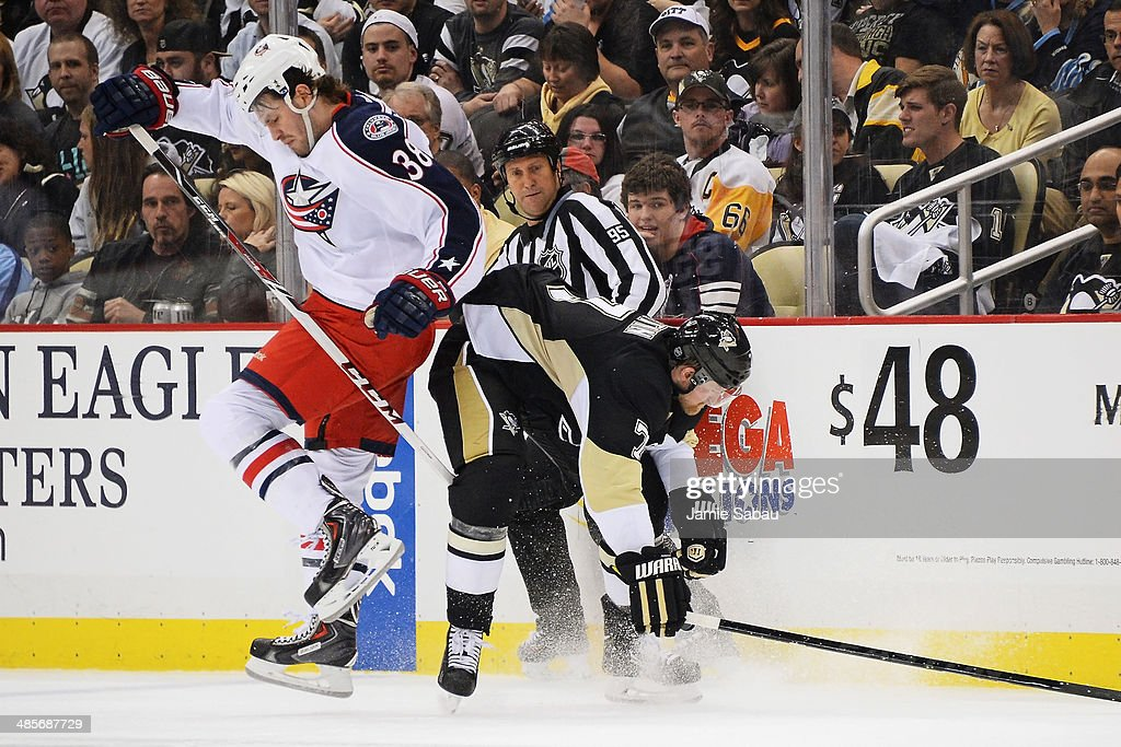Boone Jenner #38 of the Columbus Blue Jackets and Paul Martin #7 of the Pittsburgh Penguins collide near center ice in the third period in Game Two of the First Round of the 2014 NHL Stanley Cup Playoffs on April 19, 2014 at CONSOL Energy Center in Pittsburgh, Pennsylvania.