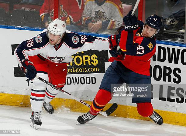 Boone Jenner of the Columbus Blue Jackets checks Colby Robak of the Florida Panthers as he passes the puck at the BBT Center on April 12 2014 in...