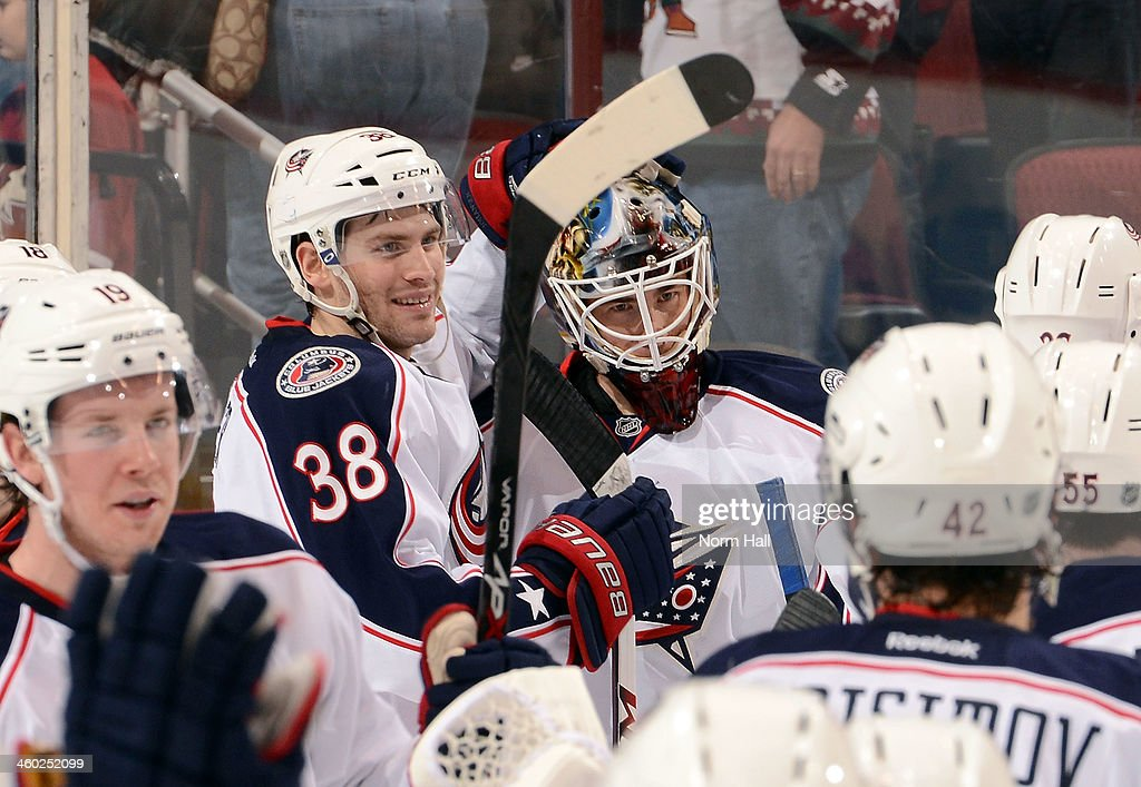 Boone Jenner #38 of the Columbus Blue Jackets congratulates goaltender Curtis McElhinney #31 after a 2-0 shutout of the Phoenix Coyotes at Jobing.com Arena on January 2, 2014 in Glendale, Arizona.