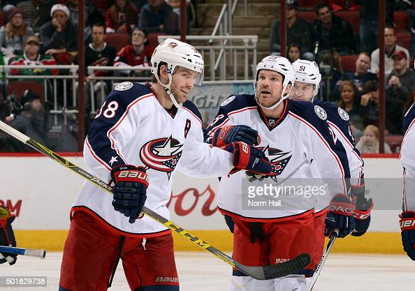 Boone Jenner of the Columbus Blue Jackets congratulates teammate David Clarkson after Clarkson's third period goal against the Arizona Coyotes at...