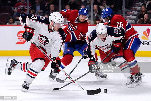 Boone Jenner of the Columbus Blue Jackets skates with the puck in front of teammate Cam Atkinson and Andrei Markov and PK Subban of the Montreal...