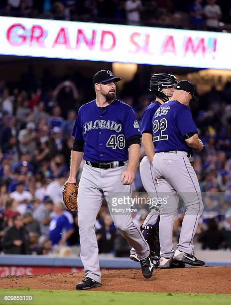 Boone Logan of the Colorado Rockies leaves the mound after giving up a grand slam homerun to Yasmani Grandal of the Los Angeles Dodgers to trail 74...