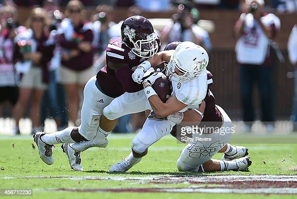 Boone Niederhofer of the Texas AM Aggies is brought down by Will Redmond and Richie Brown of the Mississippi State Bulldogs during the second quarter...