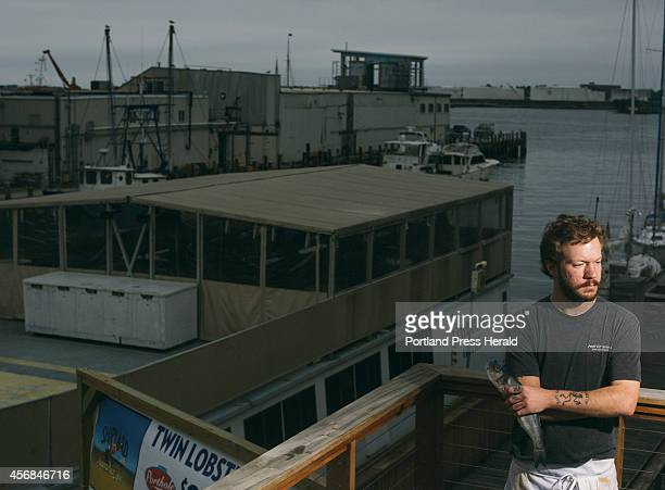 Boone's cook Dan Hebein holds a fish on the balcony of the restaurant in Portland ME on Wednesday October 1 2014 Hebein has multiple tattoos and on...