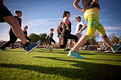 A group of people exercising and stretching in the Spanish sunshine with personal trainer.