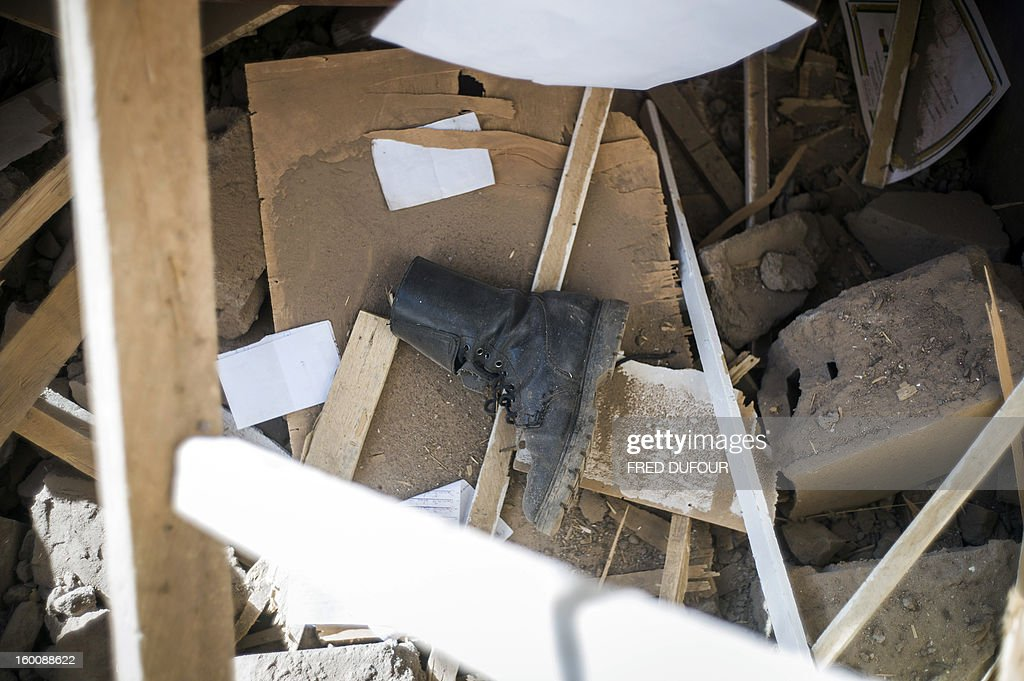 A boot lies amid debris in a destroyed area of Konna on January 26, 2013. French-led forces today wrested control of the airport at the Islamist stronghold of Gao, 1,200 kilometres (750 miles) northeast of the Mali capital Bamako, a security source said.
