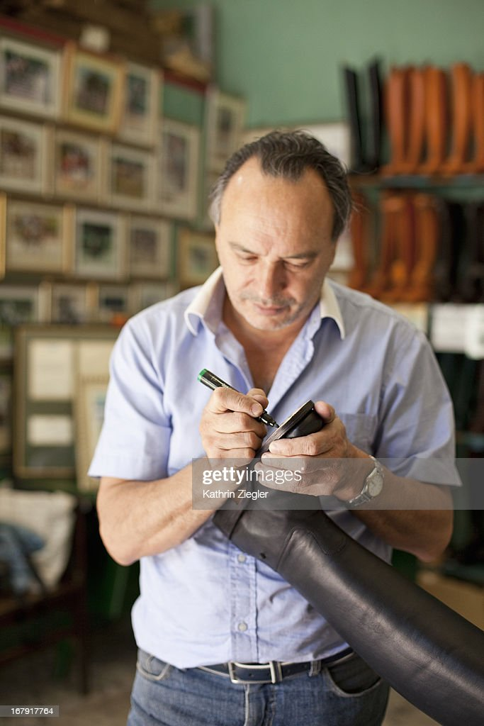 boot maker labeling sole of riding boot : Stock Photo