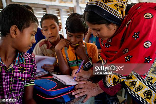 A boot school teacher explains how to do the classwork to some of the students Shidhulai Swanirvar Sangstha has developed solarpowered floating...
