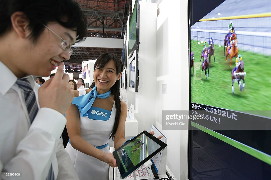 A booth assistant demonstrates Gree Inc.'s 'Million Derby' on Apple Inc.'s iPad tablet computer at the company's booth during the Tokyo Game Show 2012 at Makuhari Messe on September 20, 2012 in Chiba, Japan. The annual video game expo, which is held from September 20 to 23, attracts thousands of business visitors and the general public with exhibitions of the upcoming game software and latest hardware.