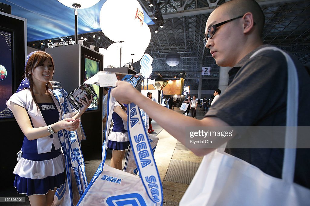 A booth assistant (L) gives out a bag to an attendee at the Sega Corp. booth during the Tokyo Game Show 2012 at Makuhari Messe on September 20, 2012 in Chiba, Japan. The annual video game expo, which is held from September 20 to 23, attracts thousands of business visitors and the general public with exhibitions of the upcoming game software and latest hardware.