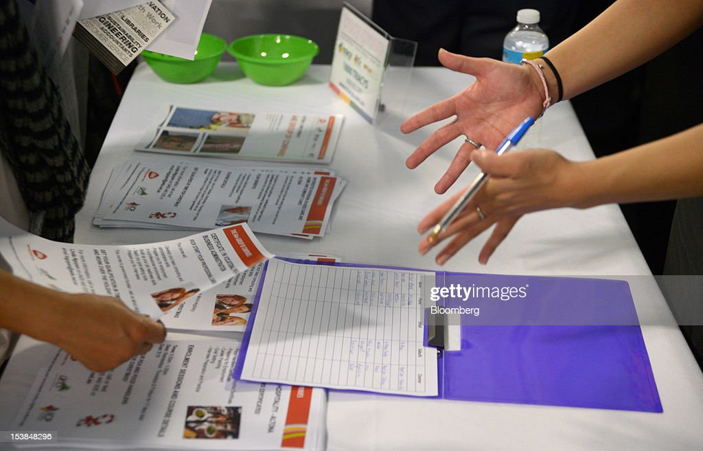 A booth attendant discusses training courses with a job seeker at a jobs and skills expo run by the Australian government in Melbourne, Australia, on Thursday, Oct. 4, 2012. Australia's unemployment rate probably climbed to 5.3 percent last month from 5.1 percent in August, according to the median estimate of economists surveyed by Bloomberg News. Photographer: Carla Gottgens/Bloomberg via Getty Images