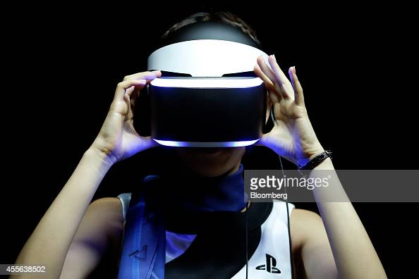 A booth attendant wears the Sony Corp Project Morpheus virtual reality headset during a demonstration for a photograph at the Tokyo Game Show 2014 in...