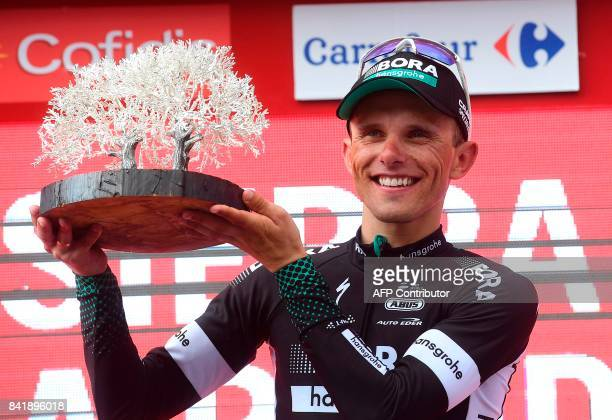 BoraHansgrohe's Polish cyclist Rafal Majka holds a trophy as he celebrates on the podium of the 14th stage of the 72nd edition of 'La Vuelta' Tour of...