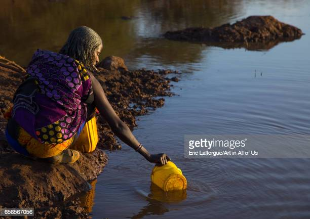 Borana tribe woman filling jerricans in a water reservoir used for animals Oromia Yabelo Ethiopia on March 5 2017 in Yabelo Ethiopia