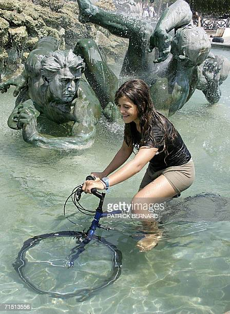A young lady tries to ride her bicycle in the fresh water of a fountain in Bordeaux 25 July 2006 Europeans struggled through another day of blazing...