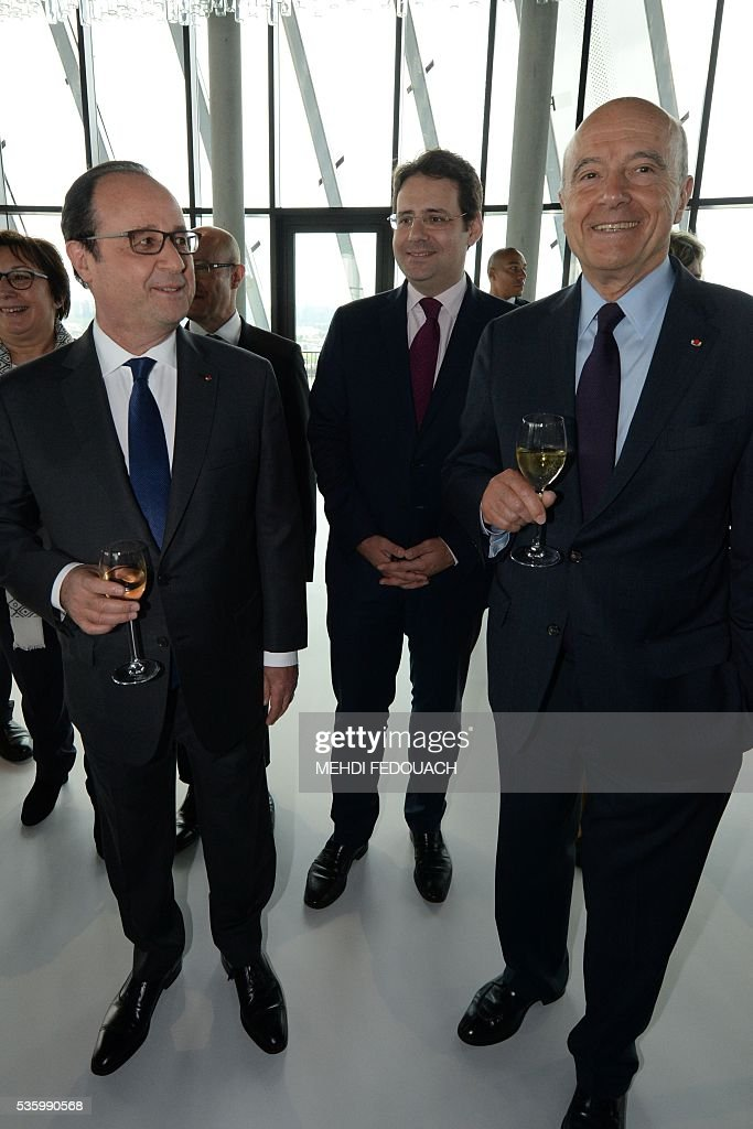 Bordeaux mayor Alain Juppe (R) and French President Francois Hollande (L) raise a toast as French junior minister for Foreign Trade, the Promotion of Tourism and French Nationals Abroad, Matthias Fekl (C) looks on, during the inauguration of the Cite du Vin (Wine Museum) on May 31, 2016 in Bordeaux. New cultural, touristic and architectural symbol of Bordeaux, the Wine Museu wishes to attract 450,000 visitors per year, is set to open on June 1 following its inauguration by Francois Hollande. / AFP / POOL / MEHDI