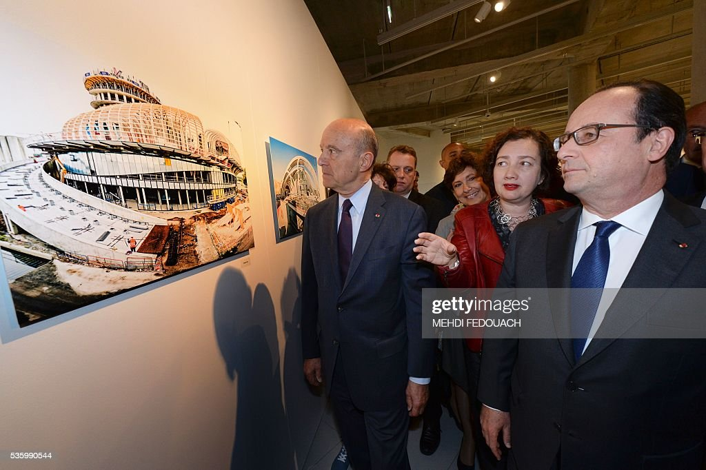 Bordeaux mayor Alain Juppe (L), French President Francois Hollande (R) and President of the Cite du Vin, Sylvie Cazes (Rear C) view a sketch of the Cite du Vin (Wine Museum) during the museum's inauguration on May 31, 2016 in Bordeaux. New cultural, touristic and architectural symbol of Bordeaux, the Wine Museu wishes to attract 450,000 visitors per year, is set to open on June 1 following its inauguration by Francois Hollande. / AFP / POOL / MEHDI