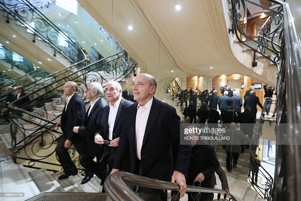 Bordeaux mayor and founder of the French opposition right-wing UMP party, Alain Juppe (foreground), is welcomed by journalist Jean-Pierre Elkabbach (L) upon his arrival on November 25, 2012, at the headquarters of French radio station Europe 1 in Paris to participate in the 'Le Grand Rendez-Vous' program. Party heavyweight Juppe, a former premier and foreign minister, will hold a mediation meeting later in the day with the right-winger, who was declared the winner of November 22 knife-edge vote to pick a party leader, Jean-Francois Cope, and his centrist rival Francois Fillon. The talks are to establish who actually won the leadership and whether mutual allegations of ballot rigging have any foundation. AFP PHOTO / KENZO TRIBOUILLARD