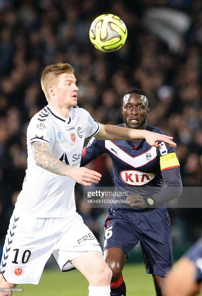 Bordeaux' s Ludovic Sane (R) vies with Reims' Gaetan Charbonnier (L) during the French L1 footbal match Bordeaux-Reims on February 28, 2014 at the Chaban Delmas Stadium in Bordeaux southwestern France.