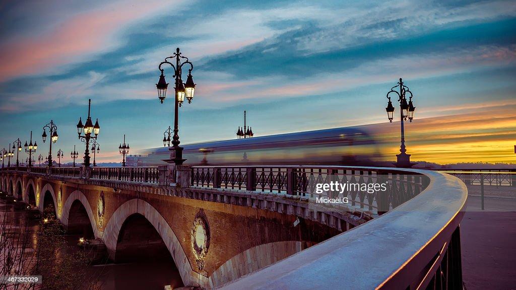 Bordeaux tram passing over the stone bridge at daw