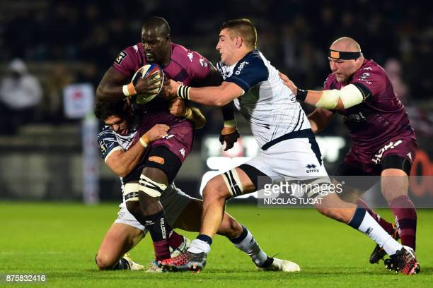 BordeauxBegles' French flanker Mahamadou Diaby is tackled by Agen's players during the French Top 14 rugby union match between BordeauxBegles and...