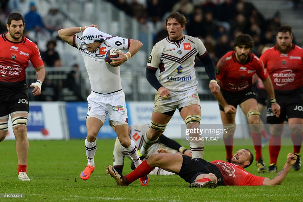 Bordeaux-Begles' French scrumhalf Yann Lesgourgues (L) runs with the ball as he removes his jersey from over his eyes during the French Top 14 rugby union match between Bordeaux-Begles and Toulon on February 14, 2016 at the Matmut Atlantique stadium in Bordeaux, southwestern France. AFP PHOTO / NICOLAS TUCAT / AFP / NICOLAS TUCAT
