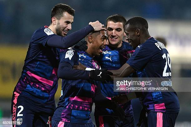 Bordeaux's Brazilian forward Malcom Silva de Oliveira is congratulated by his teammates after scoring a goal during the French L1 football match...