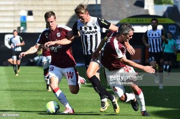 Bordeaux's French defender Maxime Poundje and Bordeaux's French midfielder Jeremy Toulalan vie for the ball with Angers' Belgian forward Baptiste...