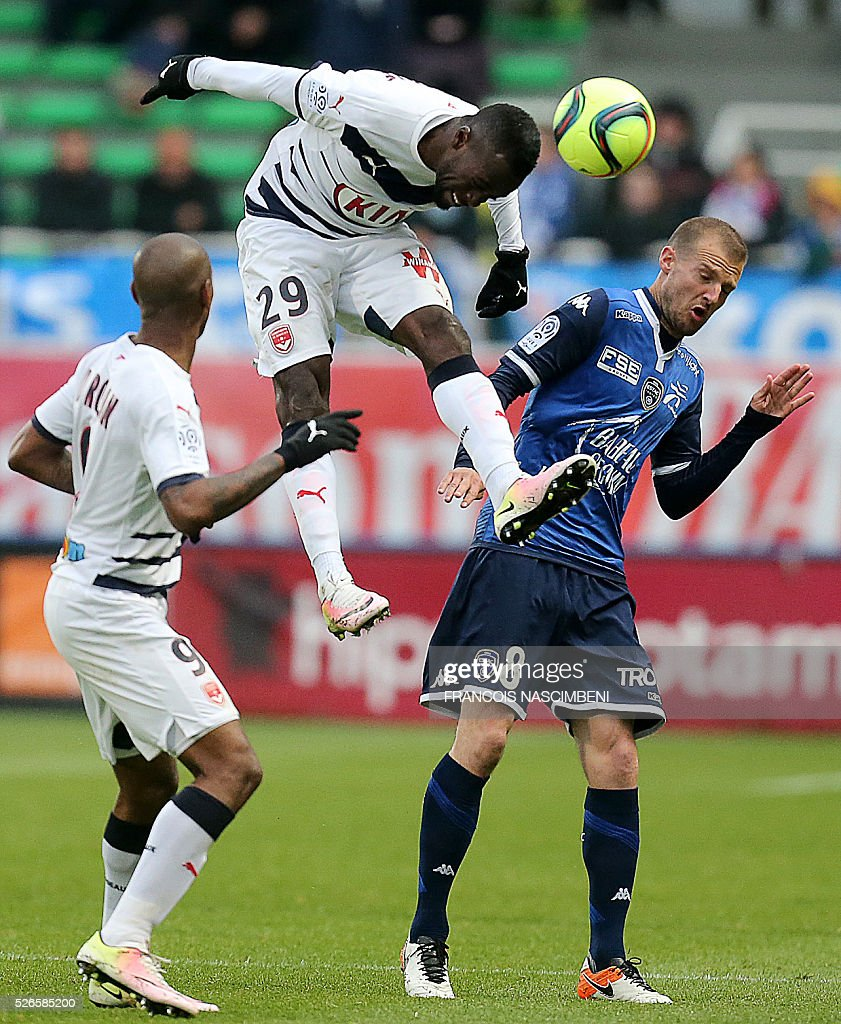 Bordeaux's French defender Maxime Poundje (C) jumps for the ball next to Troyes' French midfielder Stephane Darbion (R) during the French L1 football match between Troyes (ESTAC) and Bordeaux (FCGB) on April 30, 2016 at the Aube Stadium in Troyes, eastern France.