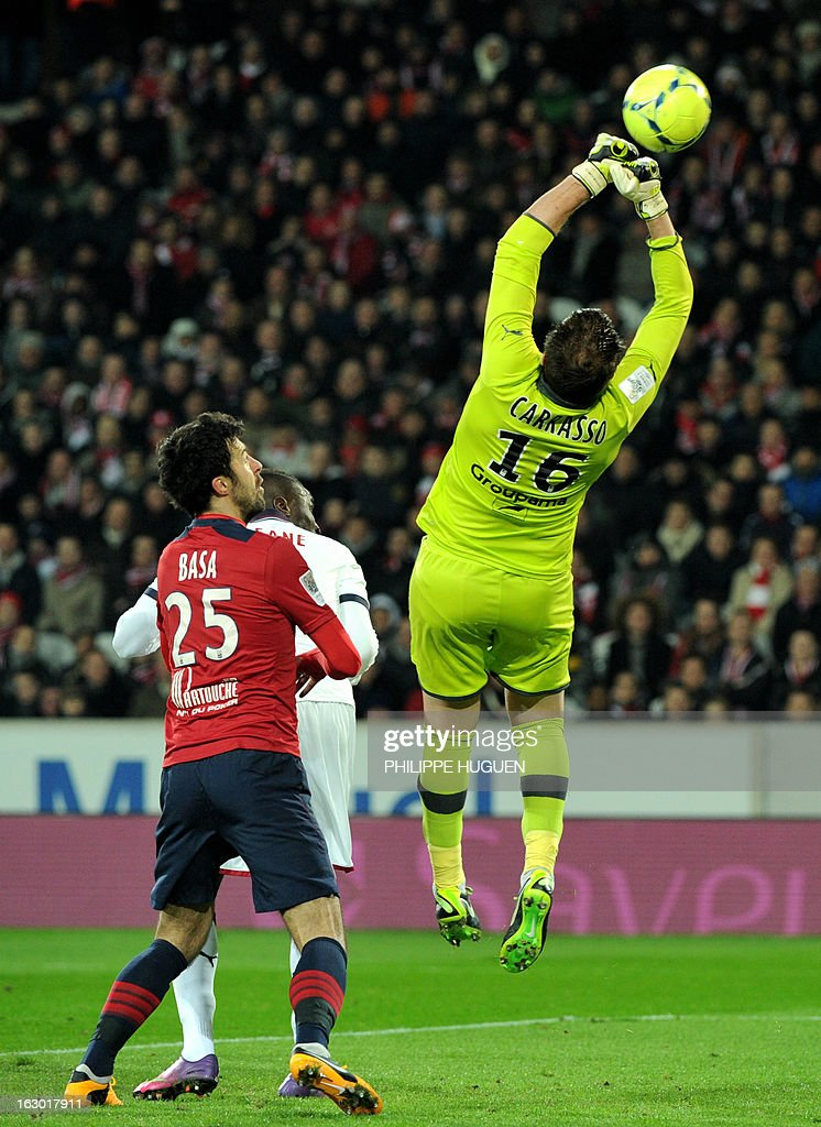 Bordeaux's French goalkeeper Cedric Carrasso (R) jumps up to block the ball near Lille's Montenegrin defender Marko Basa during the French L1 football match Lille vs Bordeaux on March 3, 2013 at the Grand Stade in Villeneuve d'Ascq.