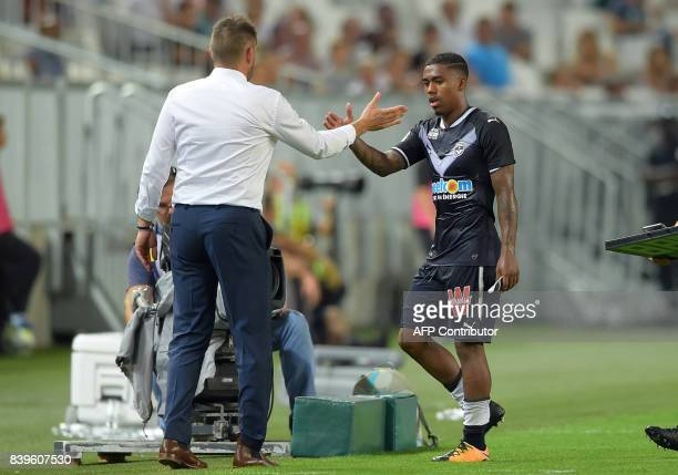 Bordeaux's French head coach Jocelyn Gourvennec shakes hands with Bordeaux's Brazilian forward Malcom during the French L1 football match between...