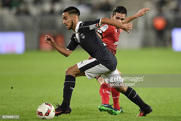 Bordeaux's French midfielder Adam Ounas challenges Dijon's FrenchAlgerian midfielder Mehdi Abeid during the French L1 football match between Bordeaux...